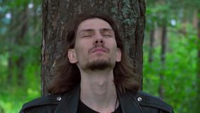 The guy in the leather jacket in the woods. Cool guy in a leather jacket in the woods among the pines stock footage