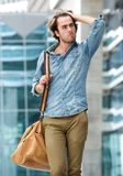 Cool guy posing with bag outdoors Stock Image