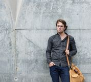 Cool guy posing with bag outdoors Royalty Free Stock Photo