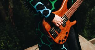 Cool guy in a raincoat jumps and plays bass guitar. Very fun and emotional. Plan in motion. stock footage