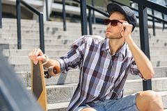 Cool guy relaxing on steps wit skate. Confident young man is waiting for someone on staircase. He is sitting and holding skateboard. Skater is touching Royalty Free Stock Images