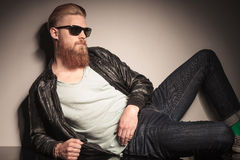 Cool guy resting on studio floor. Cool guy with long red beard, in leather jacket, resting on the floor, looking away Stock Photo