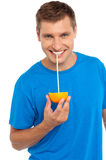 Cool guy sipping juice from half orange. Using straw to sip royalty free stock photo