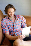 Cool guy sitting on couch with digital tablet Stock Photography