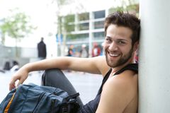 Cool guy sitting outdoors with bag. Close up portrait of a cool guy sitting outdoors with bag Royalty Free Stock Image