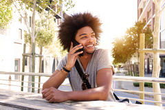 Cool guy sitting outside talking on cell phone Stock Photo