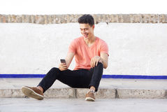 Cool guy sitting on sidewalk looking at mobile phone Royalty Free Stock Photo