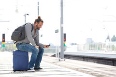 Cool guy sitting on suitcase waiting for train Royalty Free Stock Photos