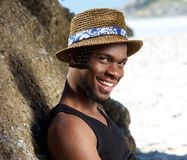 Cool guy smiling at the beach with hat Stock Image