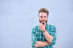 Cool guy smiling with hand on chin Royalty Free Stock Photography