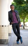 Cool guy smiling outdoors in black leather jacket. Full length portrait of a cool guy smiling outdoors in black leather jacket Stock Photography