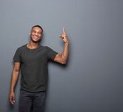 Cool guy smiling and pointing finger. Portrait of a cool guy smiling and pointing finger on copy space gray background Royalty Free Stock Images
