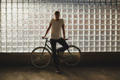 Cool boy standing with classic bicycle and thoughtfully looking in camera. Photo of young man in white t-shirt leaning. Cool guy standing with classic bicycle Royalty Free Stock Images