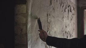 Cool guy with a view of the killer is on the shabby corridor in an abandoned building. Holding a knife to the wall stock video footage