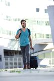 Cool guy walking with suitcase and bag Stock Photo