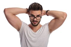 Cool guy wearing glasses down stands  with hands behind head. Cool guy wearing glasses down is standing with hands behind head on white background Stock Photography