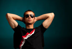 Cool guy wearing sunglasses. And relaxing against the blue background Royalty Free Stock Photography