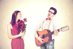 Cool guy winning His Woman with a sweet serenade in a valentine`s day. Cool guy winning His Woman with a serenade in a valentine`s day royalty free stock image