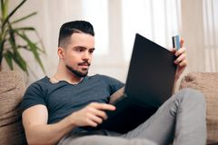 Man Sitting on a Couch Using His Laptop royalty free stock photos