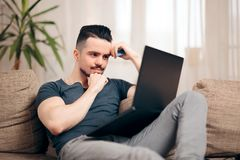 Man Sitting on a Couch Using His Laptop stock photos