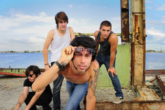Cool guys team posing. Portrait of young trendy team of male friends posing on grunge urban background stock photos