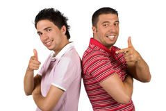 Cool guys thumbs-up and point. Two cool guys pointing and give thumbs-up same time and standing back to back smiling and facing camera isolated on white Royalty Free Stock Photography
