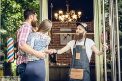 Cool hairstylist giving a fist bump to a happy customer at the door stock photos