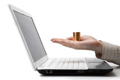 mans hand holding a stack of coins on a laptop Royalty Free Stock Photography