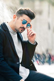 Cool handsome fashion young man. Stylish man in the city. A charming young stylish man with sunglasses. Sitting position, confident attitude with setting in the Royalty Free Stock Photos