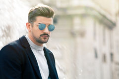 Cool handsome fashion young man. Stylish man with sunglasses. A charming young stylish man with sunglasses. Confident attitude with setting in the historic city Stock Images