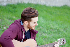 Cool handsome guy with beard playing guitar Royalty Free Stock Photography