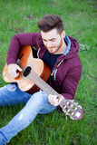 Cool handsome guy playing guitar at outside Royalty Free Stock Photography