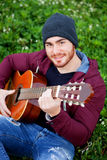 Cool handsome guy playing guitar at outside Stock Photos