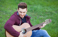 Cool handsome guy playing guitar at outside Royalty Free Stock Images