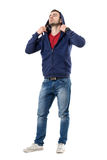 Cool handsome man putting on hoodie of blue sweatshirt looking up. Royalty Free Stock Image