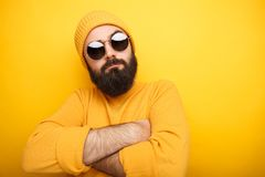 Cool bearded man in sunglasses. Cool handsome man in yellow clothes and sunglasses posing with arms crossed Stock Photography
