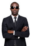 Cool and handsome. Serious young African man in formalwear and sunglasses keeping arms crossed and looking at camera while standing isolated on white background stock image