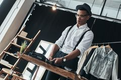 Cool and handsome. Serious young man arranging menswear while st. Anding in the showroom Royalty Free Stock Photography