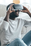 Cool!. Handsome young African man adjusting his VR headset while sitting on the carpet at home Stock Photos