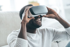 This is cool!. Handsome young African man adjusting his VR headset and smiling while sitting on the carpet at home Royalty Free Stock Image