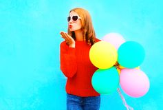 Cool happy gir lsends an air kiss with colorful balloons on blue Stock Photo