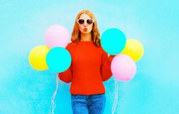 Cool happy girl does an air kiss with colorful balloons on blue Royalty Free Stock Images