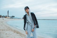 Cool and hip hipster young woman in tracksuit. Happy and natural beauty young pretty and attractive woman or teenager wears grey hoodie and sweatpants during Royalty Free Stock Image