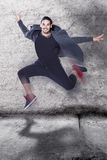Cool hip-hop dancer jumping. Against grunge wall Stock Photo
