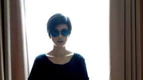 Cool hipster Asian woman wearing sunglasses with backlighting stock images
