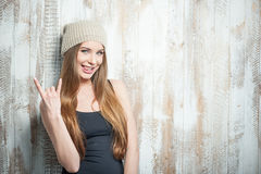 Cool hipster woman with nice hat is gesturing. Waist up portrait of beautiful hipster girl with nice hat, who is showing a gesture that symbolizes adoring rock Royalty Free Stock Images