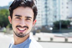 Cool hispanic guy in a grey shirt in city Royalty Free Stock Images
