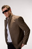 Cool hunk with sunglasses. Handsome Caucasian man in brown suit and sunglasses Royalty Free Stock Photo