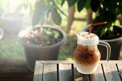 Cool ice caramel macchiato coffee on rough wooden table in topical garden. Stock Photos