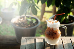 Cool ice caramel macchiato coffee on rough wooden table in topical garden. Royalty Free Stock Image